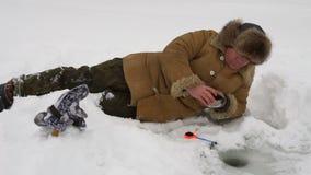 El pescador coge un pescado en la pesca del hielo almacen de metraje de vídeo