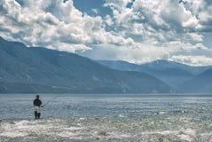 El pescador coge un pescado en el lago grande Foto de archivo libre de regalías