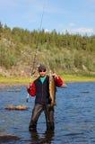 El pescador cogió un salmón en el río del norte Imagenes de archivo