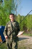 El pescador cogió una carpa de los pescados en manos Fotos de archivo
