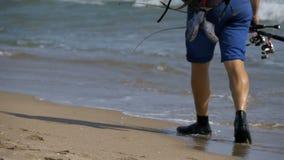 El pescador con cañas de pescar y una mochila camina a lo largo de la playa de la orilla de mar Cámara lenta almacen de video
