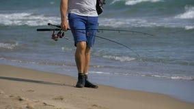 El pescador con cañas de pescar y una mochila camina a lo largo de la playa de la orilla de mar Cámara lenta almacen de metraje de vídeo
