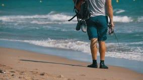 El pescador con cañas de pescar y una mochila camina a lo largo de la playa de la orilla de mar Cámara lenta metrajes