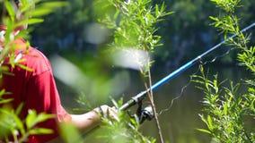 El pescador con una caña de pescar está en la orilla del río Paisaje hermoso del verano Reconstrucción al aire libre manía metrajes