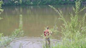 El pescador con una caña de pescar está en la orilla del río Paisaje hermoso del verano Reconstrucción al aire libre manía almacen de metraje de vídeo