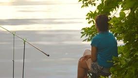 El pescador de la muchacha del estudiante está pescando en el banco del río, lago almacen de metraje de vídeo