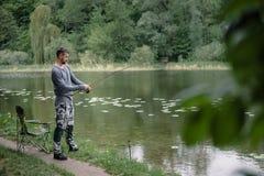 El pescador echó la caña de pescar en agua del lago o de río Hombre con los trastos de giro en forma de vida sana del bosque verd imagenes de archivo
