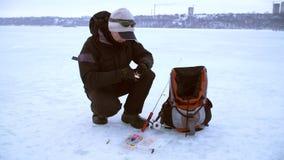 El pescador elige cebo en boca de la caja y de los cambios metrajes