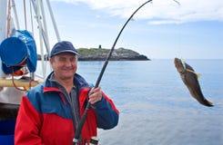 El pescador en el barco en el fiordo noruego Imagen de archivo libre de regalías