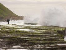 El pescador en las rocas en la marea primavera-baja en la reunión oscila, Durban, Suráfrica Fotografía de archivo libre de regalías