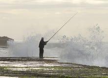 El pescador en las rocas en la marea primavera-baja en la reunión oscila, Durban, Suráfrica Foto de archivo
