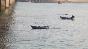 el pescador en máscara pesca con la aterrizaje-red debajo del puente metrajes