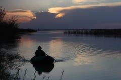 El pescador en un barco Fotos de archivo