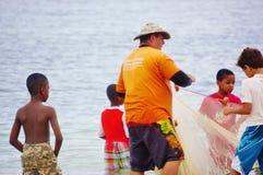 El pescador enseña a niños a utilizar la red Foto de archivo libre de regalías