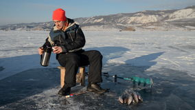 El pescador es un hombre en la pesca del invierno almacen de metraje de vídeo