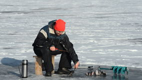 El pescador es un hombre en la pesca del invierno almacen de video