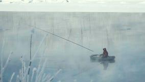 El pescador está pescando en el río del barco Pesca del invierno metrajes