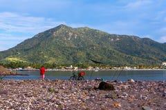 El pescador fija el cebo en su trole en la playa de Manzanillo Colima imagenes de archivo