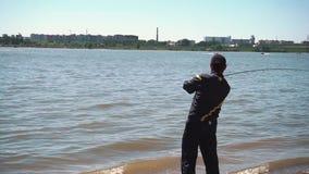 El pescador lanza aparejos de pesca en el río en el amanecer almacen de metraje de vídeo