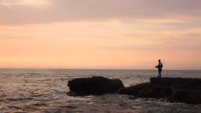El pescador lanza una caña de pescar en el mar que se coloca en las rocas Cámara lenta almacen de metraje de vídeo