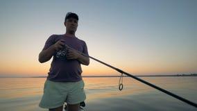 El pescador masculino está aspando una bobina trole en el proceso de la pesca almacen de metraje de vídeo