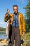 El pescador pesa un salmón hermoso Imágenes de archivo libres de regalías