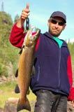 El pescador pesa un salmón masculino grande Fotografía de archivo