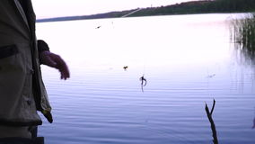 El pescador pone gusanos como cebo para los pescados en la barra del gancho metrajes