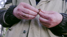 El pescador pone gusanos como cebo para los pescados en la barra del gancho almacen de video