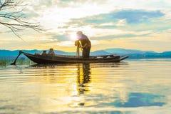 El pescador prepara la red en barco viejo el madrugada del lago imágenes de archivo libres de regalías