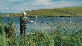 El pescador puso una línea hacia fuera con trole en el lago almacen de video