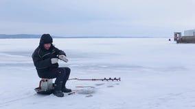 El pescador se sienta en el río congelado y los pescados de las capturas después él pone la caña de pescar del invierno en el hie almacen de video