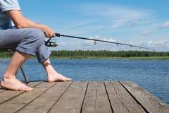 El pescador se sienta en una silla y coge pescados del embarcadero en el cebo imagenes de archivo