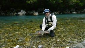 El pescador sostiene una trucha marrón grande metrajes