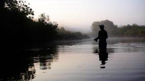 El pescador va pesca con mosca en el río de la mañana almacen de video