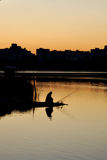 el pescador y la salida del sol sobre el agua Imágenes de archivo libres de regalías