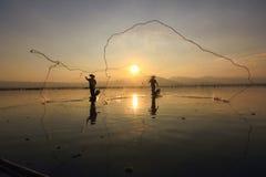 El pescar con caña de dos pescadores sobre el lago Foto de archivo