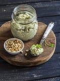 El pesto vegetariano delicioso de las nueces del bróculi y de pino sauce en tablero rústico de madera imagenes de archivo
