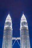 El Petronas se eleva en la noche, Petronas que las torres gemelas son rascacielos gemelos en Kuala Lumpur, Malasia Fotografía de archivo