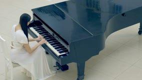 El pianista de la muchacha en el piano Ninguna cara 4K almacen de video
