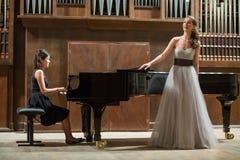 El pianista de la mujer juega el piano y al cantante hermoso Foto de archivo