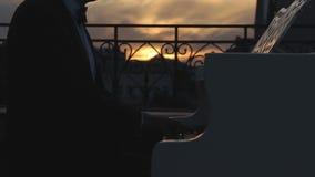 El pianista juega el piano en la puesta del sol almacen de metraje de vídeo