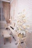 El piano blanco cerca adornó el árbol de navidad Foto de archivo