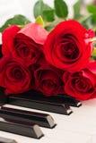 El piano de las rosas rojas cierra el fondo romántico Imagen de archivo libre de regalías