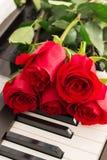 El piano de las rosas rojas cierra el fondo romántico Imagenes de archivo