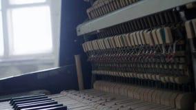 El piano de madera roto clásico con llaves polvorientas, abre los martillos y las secuencias interiores almacen de video
