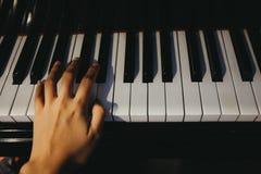 El piano del juego de la mano izquierda del uso de la mujer joven tiene llave del piano es backgroun Fotografía de archivo libre de regalías