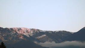 El pico de montaña nevado se encendió por el sol de la mañana almacen de video