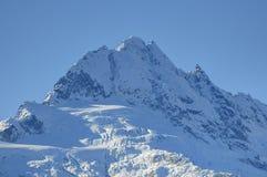 El pico de Mt Tantalus en el extremo meridional de las montañas costeras de la Columbia Británica, Canadá contra el cielo azul fotos de archivo