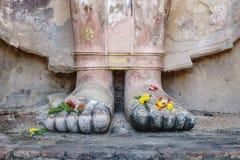 El pie de la estatua antigua magnífica de Buda con las flores para ruega Fotografía de archivo